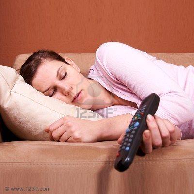 4194195 una giovane donna dormendo su un divano davanti a un televisore con il telecomando che scivola fuori