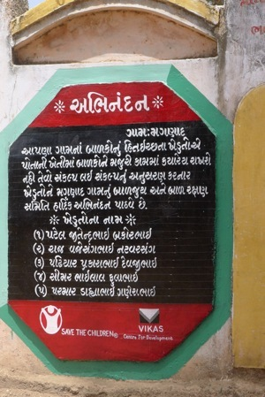 Working with farmers to change community attitudes about child labour is a key part of the programme's success. This sign, hanging in Magnad village, provides positive recognition to five local farmers who have pledged not to use child labour.