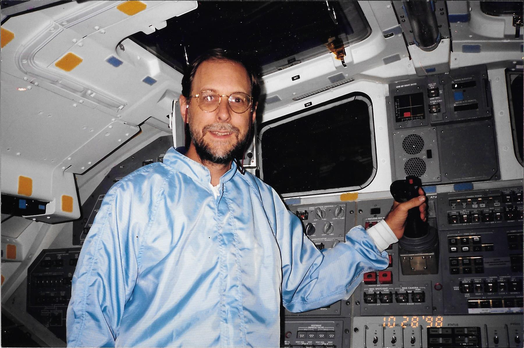 "On the flight deck of the Orbiter Atlantis, in a rare shot without an ""eyes only� hood or gloves. Due to my excessive hairiness, I was normally required to wear a hood whenever on board!"