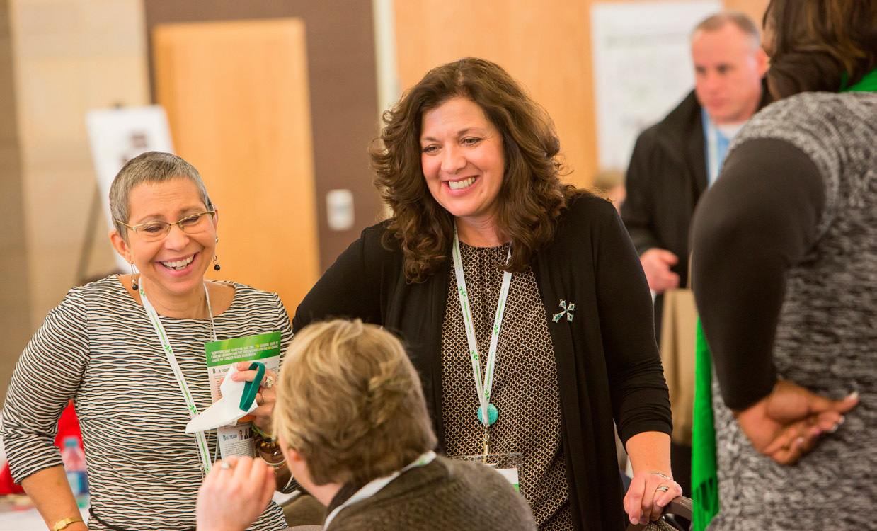 """MELINDA BACHINI (center), whose cholangiocarcinoma has responded to immunotherapy, mingles with attendees at the Cholangiocarcinoma FoundationAnnual Conference. PHOTO BY BARR PHOTOGRAPHY (COURTESY OFTHE CHOLANGIOCARCINOMA FOUNDATION"""