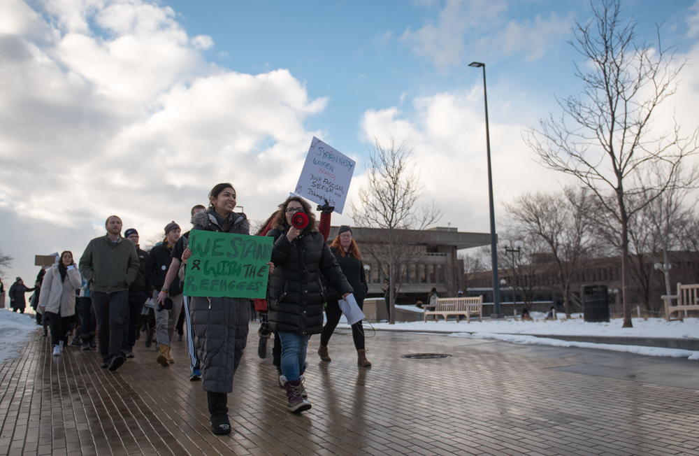 "Arva Hassonjee (green sign) and Nedda Sarshar (megaphone) lead hundreds of students down Syracuse University's promenade on Thursday, Feb. 2, 2017 in a ""Rally for Refugees"" protest that they organized. The protest wound its way to the Life Sciences buildi"