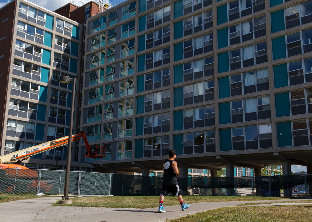 A student passes by DellPlain Hall, where work continues to upgrade the building's dorms before the fall semester starts.