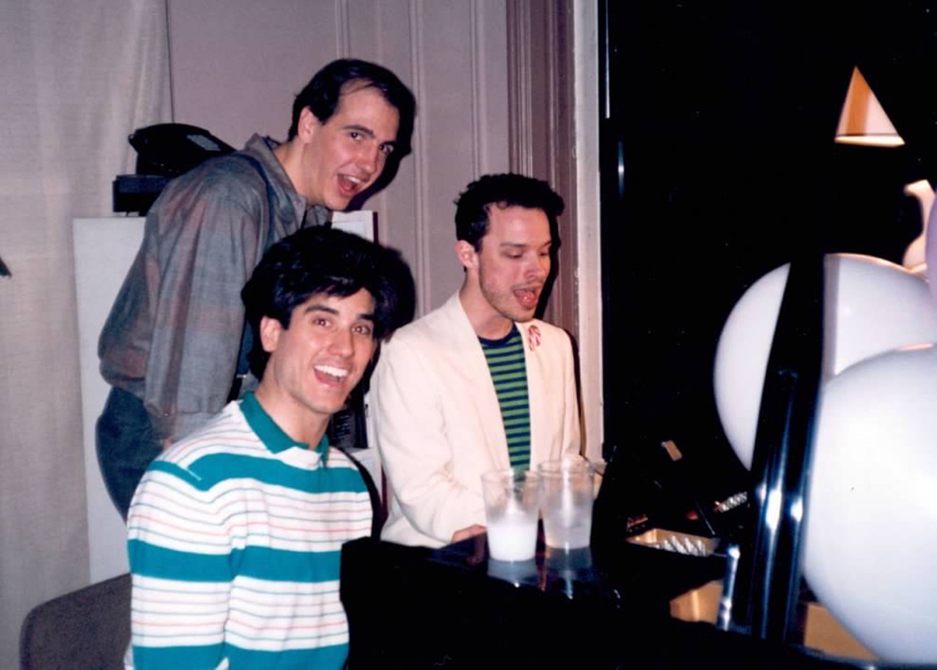 Photograph of Paul Perry playing the piano next to Sam Lloyd and George Miserlis
