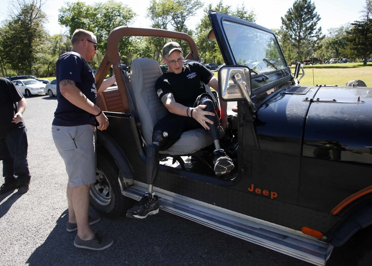 Sgt. Matt Krumwiede (R) prepares to leave for a picnic with his brother Sgt. Mark Krumwiede in Pocatello, Idaho, June 29, 2014. Krumwiede was on patrol in Afghanistan in 2012 when he stepped on an improvised explosive device which tore away both his legs, damaged his left arm, and ripped open his abdominal cavity. Since then he has undergone dozens of surgeries and spent time recovering at Brooke Medical Center in San Antonio, Texas, learning to walk again with the use of prosthetic legs. In June 2014, he visited to his hometown of Pocatello, Idaho for the first time since he was injured. Picture taken June 29, 2014. (Jim Urquhart/Reuters)