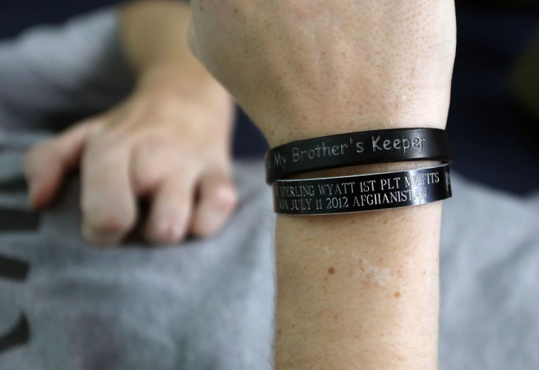 Sgt. Matt Krumwiede wears a wrist band in memory of his friend Sterling Wyatt who was killed in Afghanistan while Krumwiede does physical therapy at the Center for the Intrepid at Brooke Army Medical Center in San Antonio, Texas, February 24, 2014. Krumwiede was on patrol in Afghanistan in 2012 when he stepped on an improvised explosive device which tore away both his legs, damaged his left arm, and ripped open his abdominal cavity. Since then he has undergone dozens of surgeries and spent time recovering at Brooke Medical Center in San Antonio, Texas, learning to walk again with the use of prosthetic legs. In June 2014, he visited to his hometown of Pocatello, Idaho for the first time since he was injured. Picture taken February 24, 2014. (Jim Urquhart/Reuters)