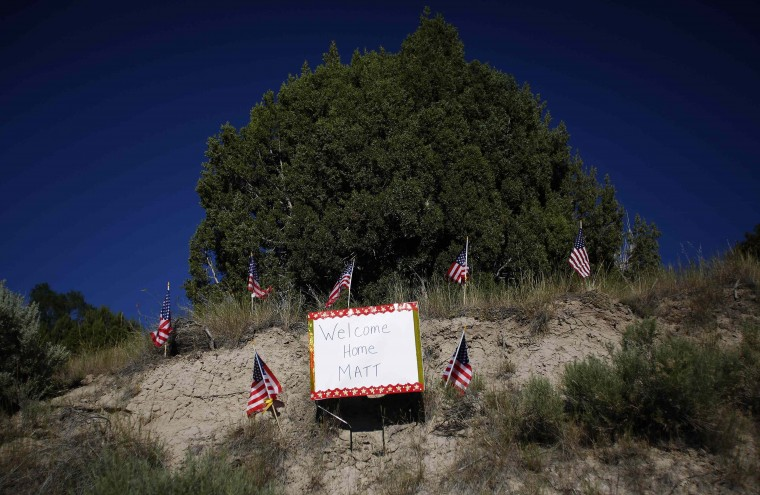 A welcome sign is seen in front of Sgt. Matt Krumwiede's home in Pocatello, Idaho, June 30, 2014. Krumwiede was on patrol in Afghanistan in 2012 when he stepped on an improvised explosive device which tore away both his legs, damaged his left arm, and ripped open his abdominal cavity. Since then he has undergone dozens of surgeries and spent time recovering at Brooke Medical Center in San Antonio, Texas, learning to walk again with the use of prosthetic legs. In June 2014, he visited to his hometown of Pocatello, Idaho for the first time since he was injured. Picture taken June 30, 2014. (Jim Urquhart/Reuters)
