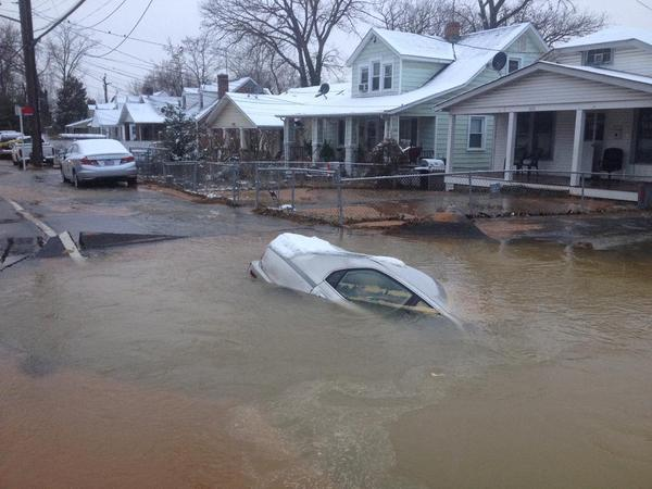 An NBC Washington photo shows a car swallowed up by a sinkhole that was caused by a water main break in Bladensburg. (NBC Washington)