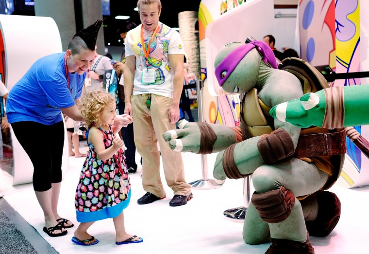 Two year old Ellie Campbell, along with her aunt Jen Pike of Austin, Texas, gets a high-five from the Teenage Mutant Ninja Turtle character Donatello during the 45th annual San Diego Comic-Con on July 24, 2014 in San Diego, California. An estimated 130,000 attendees are expected at this year's convention, which will celebrate the 75th anniversary of both Marvel Comics and the first Batman comic book. (T.J. Kirkpatrick/Getty Images)