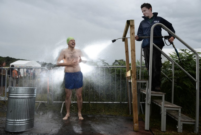 An entrant is hosed down after takes part in the Irish Bog Snorkelling championship this afternoon at Peatlands Park on July 27, 2014 in Dungannon, Northern Ireland. The annual event sees male and female competitors swim the 60m length of the bog watched by scores of spectators and takes place on International Bog Day. (Charles McQuillan/Getty Images)