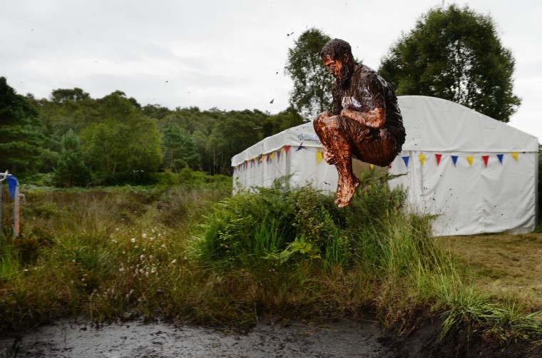 A male entrant takes a dip in the Bog Jacuzzi after takes part in the Irish Bog Snorkelling championship this afternoon at Peatlands Park on July 27, 2014 in Dungannon, Northern Ireland. The annual event sees male and female competitors swim the 60m length of the bog watched by scores of spectators and takes place on International Bog Day. (Charles McQuillan/Getty Images)
