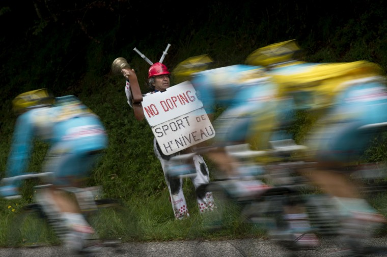 "A supporter holds a placard reading ""No doping. Top-level sport"" as Kazakhstan's Astana cyclists ride past during the 170 km ninth stage of the 101st edition of the Tour de France cycling race on July 13, 2014 between Gerardmer and Mulhouse, eastern France. (Lionel Bonaventure/Getty Images)"