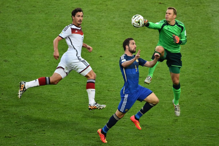 Germany's goalkeeper Manuel Neuer (R) and Argentina's forward Gonzalo Higuain (C) are watched by Germany's defender Mats Hummels (L) as they compete for the ballduring the final football match between Germany and Argentina for the FIFA World Cup at The Maracana Stadium in Rio de Janeiro on July 13, 2014. (Gabriel Bouys/Getty Images)