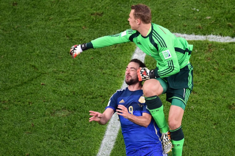 Germany's goalkeeper Manuel Neuer (R) punches the ball past Argentina's forward Gonzalo Higuain during the 2014 FIFA World Cup final football match between Germany and Argentina at the Maracana Stadium in Rio de Janeiro on July 13, 2014. (Francois Xavier Marit/Getty Images)