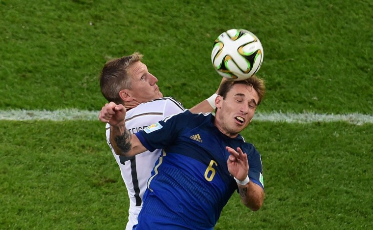 Germany's midfielder Bastian Schweinsteiger (L) and Argentina's midfielder Lucas Biglia head the ball during the final football match between Germany and Argentina for the FIFA World Cup at The Maracana Stadium in Rio de Janeiro on July 13, 2014. (Francois Xavier Marit/Getty Images)