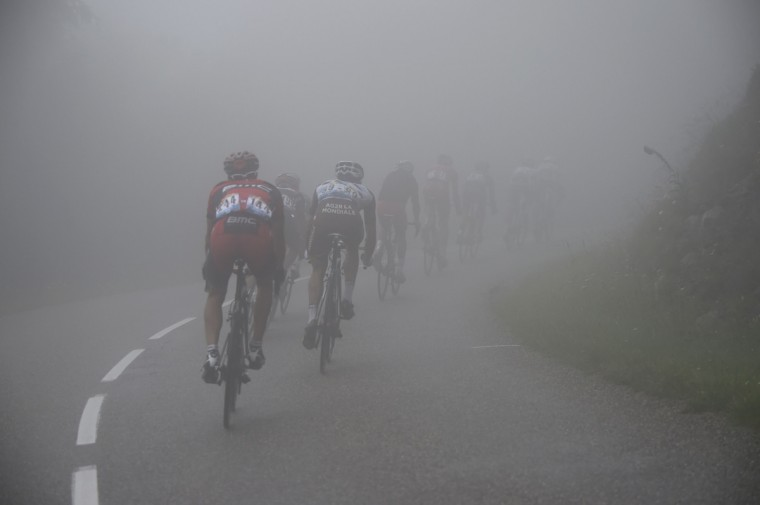 The pack rides in the fog during the 161.50 km tenth stage of the 101st edition of the Tour de France cycling race on July 14, 2014 between Mulhouse and La Planche des Belles Filles ski resort, eastern France. (Eric Feferberg/Getty Images)