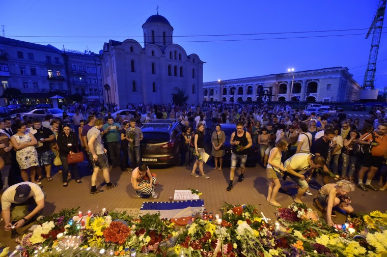 "People lay flowers and light candles in front of the Embassy of the Netherlands in Kiev on July 17, 2014, to commemorate passengers of Malaysian Airlines flight MH17 carrying 295 people from Amsterdam to Kuala Lumpur which crashed in eastern Ukraine. Ukrainian President Petro Poroshenko said on July 17 that the Malaysia Airlines jet that crashed over rebel-held eastern Ukraine may have been shot down."" Ukraine's government and pro-Russian insurgents traded blame for the disaster, with comments attributed to a rebel commander suggesting his men may have downed Malaysia Airlines flight MH17 by mistake, believing it was a Ukrainian army transport plane. (Sergei Supinsky/Getty Images)"
