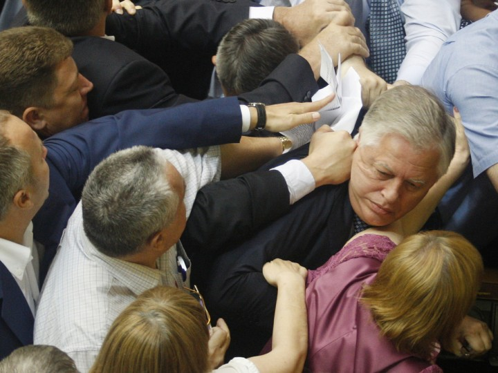 """Deputies of the All-Ukrainian Union """"Svoboda"""" party attack the head of the Communist parliamentary faction Petro Symonenko (R) as they attempt to remove him from the hall during a Ukrainian parliament sitting in Kiev on July 23, 2014. Symonenko said in an interview with Russian media that the authorities in Ukraine had killed many thousands of Ukrainians in eastern Ukraine, where they are fighting pro-Russian rebels, and is profiting from the sale of their organs. (Anatoli Stepanov/AFP/Getty Images)"""