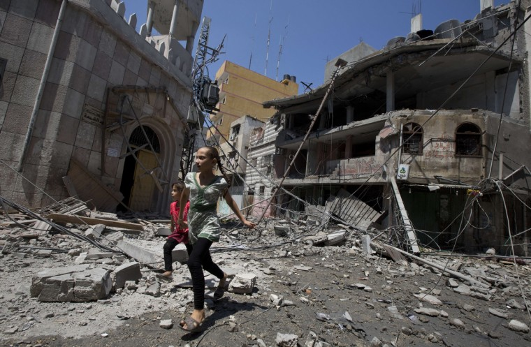 Palestinian girls walk amidst debris following an Israeli military strike in Gaza city, on July 23, 2014. Israel's deadly Gaza offensive entered its 16th day, with airlines blocking flights to Israel after a Gaza rocket struck near airport runways. UN Secretary General Ban Ki-moon expected to continue talks in Israel and US Secretary of State John Kerry due to arrive. (Mahmud Hams/AFP/Getty Images)