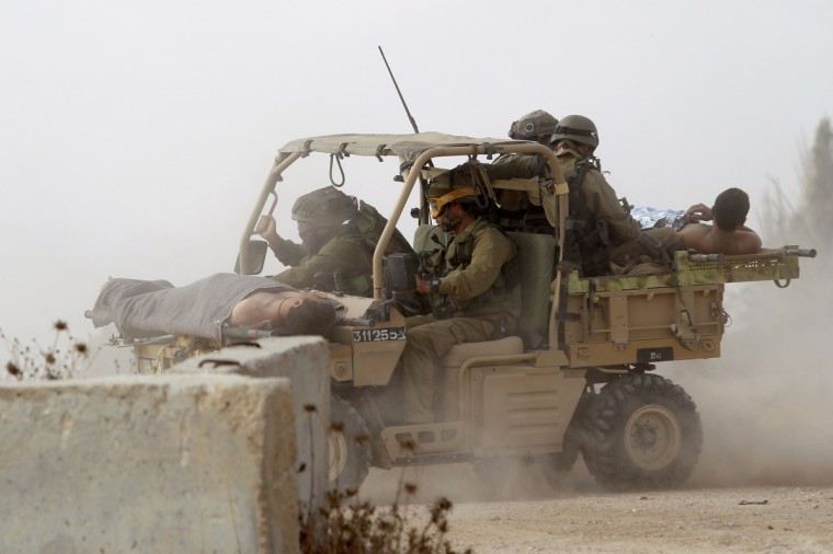 Israeli soldiers evacuate their wounded comrades at an army deployment area near Israel's border with the Gaza Strip on July 23, 2014, as the conflict entered its third week with neither side showing any sign of willingness to pull back. Israel's military pursued a relentless campaign of shelling and air strikes while the Palestinian militants hit back with rocket fire and fierce attacks on troops operating on the ground, killing 27 soldiers since the ground assault on Gaza began late on July 17. (Jack Guez/AFP/Getty Images)