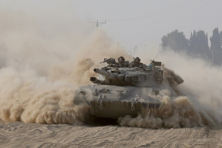 An Israeli Merkava tank rolls near Israel's border with the besieged Palestinian territory on July 23, 2014, as the conflict entered its third week with neither side showing any sign of willingness to pull back. Israel's military pursued a relentless campaign of shelling and air strikes while the Palestinian militants hit back with rocket fire and fierce attacks on troops operating on the ground. Around 650 Palestinians and 29 Israeli soldiers have been killed in the Gaza fighting which began on July 8. (Jack Guez/AFP/Getty Images)