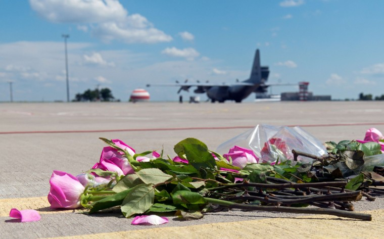 FloweRs lay on the tarmac as a ground Hercules transport aircraft of the Royal Dutch Airforce, carrying bodies from downed Malaysia Airlines flight MH17, prepares to take off from Kharkiv airport on July 23, 2014. The first plane carrying bodies from downed Malaysia Airlines flight MH17 on July 23 left eastern Ukraine for the Netherlands. The Dutch military aircraft took off from the airport in the government-controlled city of Kharkiv bound for Eindhoven after the first group of victims' remains were loaded onto the plane in wooden coffins. (Sergey Bobok/AFP/Getty Images)
