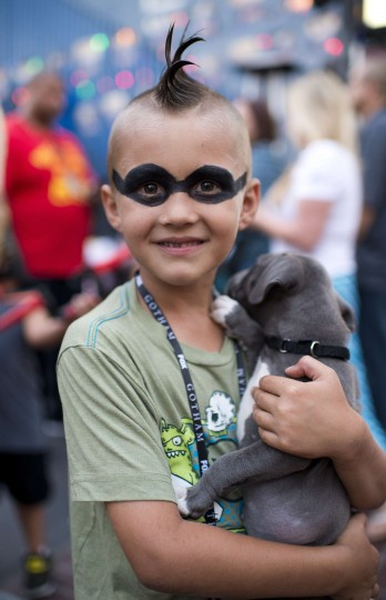 Seven-year-old Ashton Ritz cuddles with a puppy outside the San Diego Convention Center on the first day of the 45th annual Comic-Con, in San Diego, California July 24, 2014. The four-day pop culture extravaganza celebrates film, TV, video games, comic books, costumes and other popular arts. More than 150,000 fans are expected to attend the sold-out event. (Robyn Beck/AFP/Getty Images)