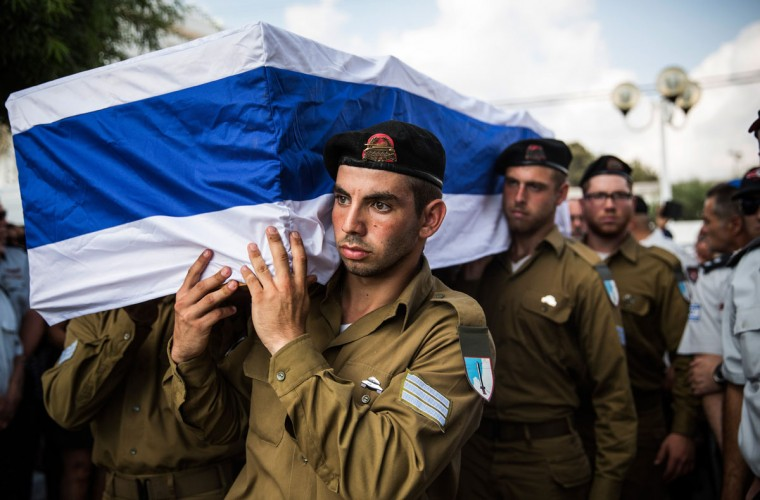 """The casket carrying Israeli Sergeant Adar Barsano is carried to a burial plot in a cemetery during his funeral on July 20, 2014 in Nahariya, Israel. Sergeant Barsano was killed along with another IDF soldier on the twelfth day of operation """"Protective Edge,"""" when Hamas militants infiltrated Israel from a tunnel dug from Gaza and engaged Israeli soldiers. (Andrew Burton/Getty Images)"""