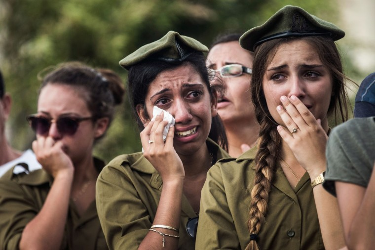 """Israeli soldiers weep at the grave of Israeli Sergeant Adar Barsano during his funeral on July 20, 2014 in Nahariya, Israel. Sergeant Barsano was killed along with another IDF soldier on the twelfth day of operation """"Protective Edge,"""" when Hamas militants infiltrated Israel from a tunnel dug from Gaza and engaged Israeli soldiers. (Andrew Burton/Getty Images)"""
