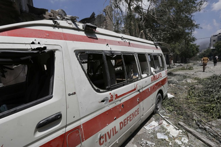 """A destroyed Civil Defence ambulance is seen on a street following an Israeli military offensive on the Shejaiya neighborhood between Gaza City and the Israeli border, which has left more than 50 people dead in a blistering bombardment which began overnight, medics said on July 20, 2014. The death toll in Gaza passed 400 as Israel pressed its biggest offensive in the enclave in five years, Palestinian health officials said. """"410 people have been killed since the war started and more than 3,020 people have been injured, most of them civilians,"""" deputy health minister Yussef Abu Rish told reporters at al-Shifa hospital in Gaza City. (Mohammed Abed/AFP/Getty Images)"""