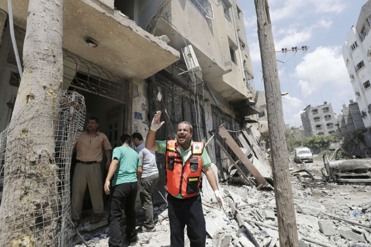 """A Civil defence worker shouts during an Israeli military offensive on the Shejaiya neighborhood between Gaza City and the Israeli border, which has left more than 50 people dead in a blistering bombardment which began overnight, medics said on July 20, 2014. The death toll in Gaza passed 400 as Israel pressed its biggest offensive in the enclave in five years, Palestinian health officials said. """"410 people have been killed since the war started and more than 3,020 people have been injured, most of them civilians,"""" deputy health minister Yussef Abu Rish told reporters at al-Shifa hospital in Gaza City. (Mohammed Abed/AFP/Getty Images)"""