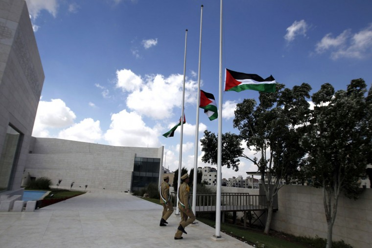 """Palestinians soldiers lower the Palestinian flags to half mast at the Muqataa Compound, on July 20, 2014, in the West Bank city of Ramallah, to show respect for all the people killed in the Gaza Strip during the Israeli military offensive """"Operation Dove"""". Palestinian president Mahmud Abbas has called for three days of mourning. (Abbas Momani/AFP/Getty Images)"""