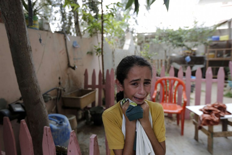The sister of Medic Fuad Jabed, who was killed while on duty in Gaza's eastern Shejaiya district, mourns during his funeral in Gaza City on July 20, 2014. At least 40 people were killed and nearly 400 wounded in Israeli shelling of Gaza's northeastern Shejaiya district overnight, medics said. (Mohammed Abed/AFP/Getty Images)