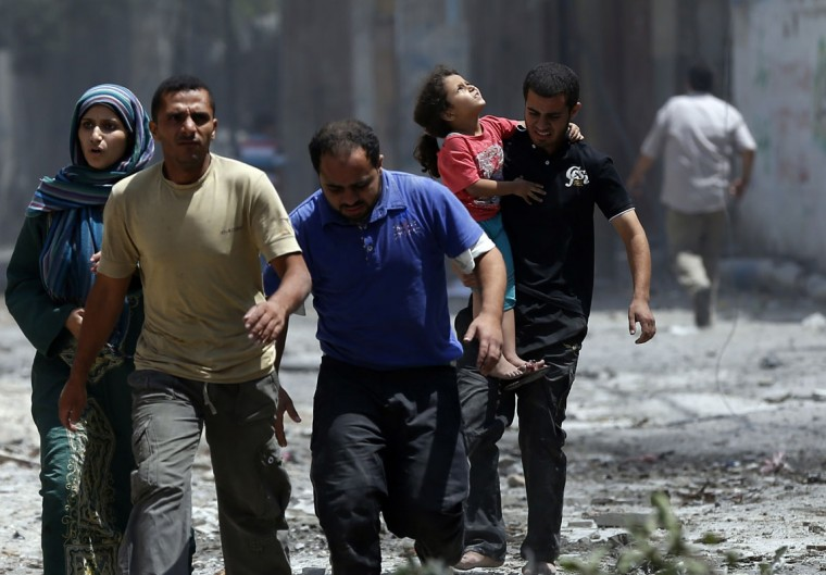 Palestinians flee from Gaza's eastern Shejaiya district on July 20, 2014. At least 40 people were killed and nearly 400 wounded in Israeli shelling of Gaza's northeastern Shejaiya district overnight, medics said. (Thomas Coex/AFP/Getty Images)