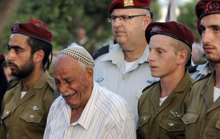 A relative mourns among comrades of Sergeant Banaya Rubel, an Israeli soldier killed during Israeli military offensive on the Gaza Strip, during his funeral in the city of Holon, near Tel Aviv on July 20, 2014. At least 97 Palestinians and 13 Israeli soldiers were killed on July 20, 2014 as Israel ramped up a major military offensive in the bloodiest single day in Gaza in five years. (David Buimovitch/AFP/Getty Images)
