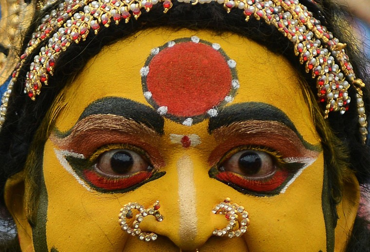 An Indian artist dressed as Hindu Goddess MahaKali performs while in a trance during the final procession of the eleven-day traditional festival of 'Bonalu', a ritual offering to the goddess MahaKali, at Sri Akkanna Madanna Mahankali Temple in Hyderabad on July, 21 2014. The Goddess is honoured mostly by women during Bonalu festival with offerings of food and dancing. (AFP PHOTO/Getty Images/Noah Seelam)