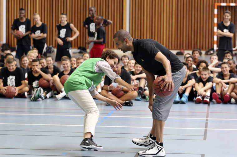 "French basketball player Tony Parker (R), point guard for the San Antonio Spurs, and French Minister of Women's Rights, Youth and Sports Najat Vallaud-Belkacem, take part in a friendly match as Vallaud-Belkacem visits the ""Tony Parker Camp"", a summer basketball camp for kids and teens, in Villeurbanne, southeastern France, on July 21, 2014. (AFP PHOTO/Getty Images/Philippe Merle)"