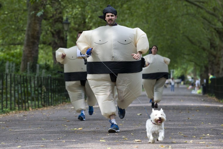 A participant runs with his dog as they take part in The Sumo Run in Battersea Park, London, on July 27, 2014. The Sumo Run is an annual 5km charity fun run around the park in inflatable sumo suits. (Justin Tallis/AFP/Getty Images)