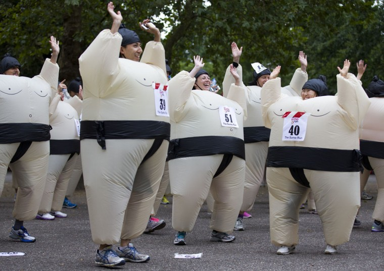 Participants warm up in inflated suits before taking part in The Sumo Run in Battersea Park, London, on July 27, 2014. The Sumo Run is an annual 5km charity fun run around the park in inflatable sumo suits. (Justin Tallis/AFP/Getty Images)