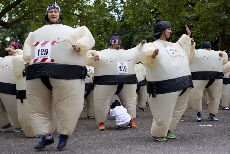 A boy crawls through a participants legs as they warm up in inflated suits before taking part in The Sumo Run in Battersea Park, London, on July 27, 2014. The Sumo Run is an annual 5km charity fun run around the park in inflatable sumo suits. (Justin Tallis/AFP/Getty Images)