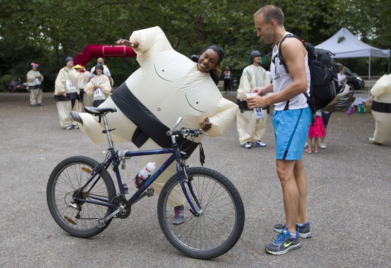 A participant attempts to mount a bike in an inflated suit before taking part in The Sumo Run in Battersea Park, London, on July 27, 2014. The Sumo Run is an annual 5km charity fun run around the park in inflatable sumo suits. (Justin Tallis/AFP/Getty Images)
