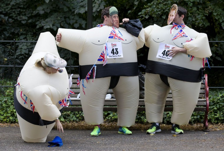 A participant bends down to pick up her hat with others wearing inflated suits and masks depicting members of the British royal family, Prince William, Duke of Cambridge, (L) Prince Philip, Duke of Edinburgh (C) and Prince Harry (R) before the start of The Sumo Run in Battersea Park, London, on July 27, 2014. The Sumo Run is an annual 5km charity fun run around the park in inflatable sumo suits. (Justin Tallis/AFP/Getty Images)