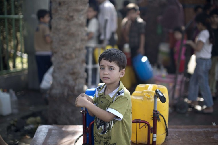 A Palestinian child waits to fill plastic bottles and water containers with drinking water from a public tap in Jabalia in the northern Gaza Strip on July 27, 2014. Three Palestinians were killed in shelling as the Israeli military resumed its assault on Gaza after Hamas shunned an extended lull accepted by Israel, medics said. Mahmud Hams/AFP/Getty Images)