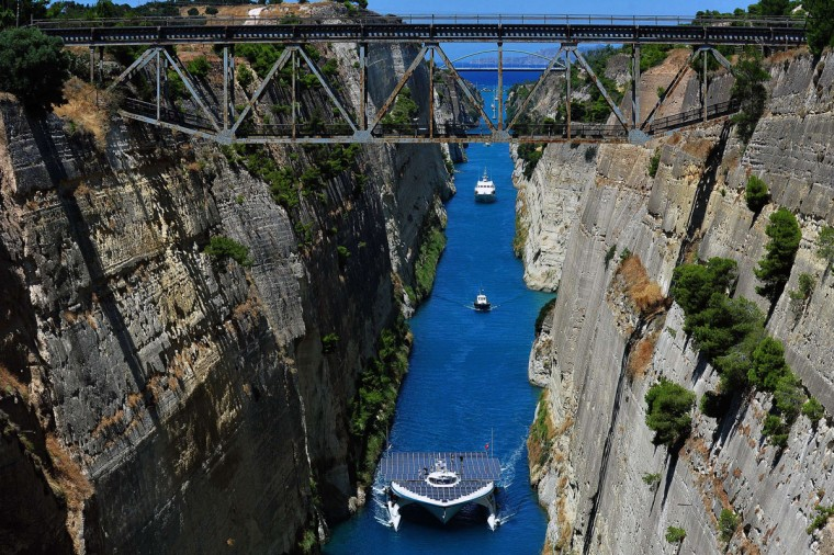 "The world's largest solar-powered boat, ""MS Turanor PlanetSolar"" sails through the Corinth Canal near the town of Corinth on July 28, 2014. The boat arrived to Greece as part of a joint archaeological project focused on underwater exploration off one of Europe's oldest human occupation sites, the Franchthi cave in the Argolid, southeast Peloponnese. The project is taking place in one of Greece's richest archaeological areas, the Argolid, known for its major palatial complexes in the Bronze Age that include Mycenae and Tiryns and later, classical-era city-states and sites like Argos and the ancient-theatre site of Epidaurus. (Valerie Gache/AFP/Getty Images)"