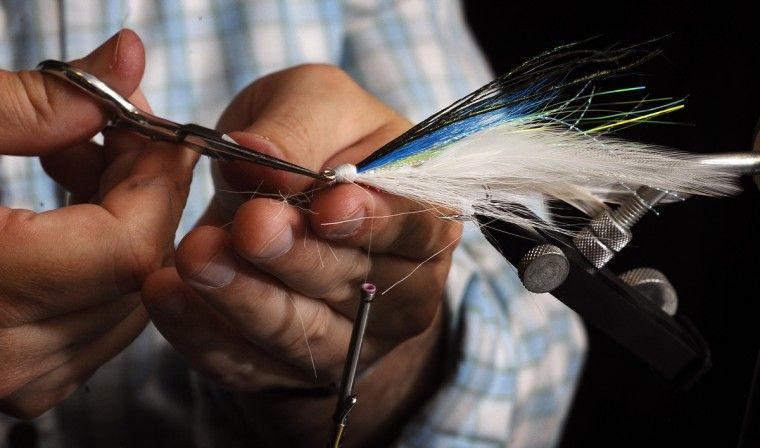 A close-up picture of Theaux Le Gardeur as he ties a Lefty Deceiver using fly-tying materials that include bird feathers, deer fur, threads, and synthetic dubbing on a hook. (Kenneth K. Lam/Baltimore Sun)