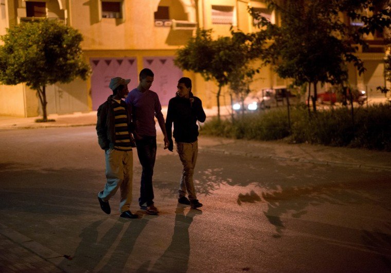 From left, Driss Hamouti, 21, takes a late night walk with his friends, Zahir Bouten, 21, and Ahraf Farithi, 19, all of Tifelt, Morocco. Driss is free to walk around at night and hang out with his friends as he pleases; the sun is no longer an issue to his skin at night. Rachel Woolf/Baltimore Sun