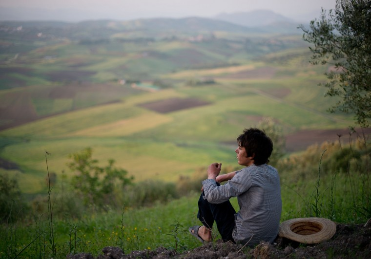 Mohamed El-Kotbi, 17, of the Province of Ouezzane, Morocco, takes a break to sit down and look at the scenery surrounding his village in the shade. El-Kotbi is more active during overcast skies or in shady areas due to his skin condition, XP. Rachel Woolf/Baltimore Sun