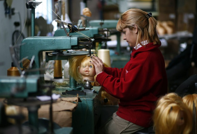 An employee sews a doll's hair to its head inside the toy factory owned by Norberto Garcia in Buenos Aires, July 28, 2014. Garcia was poised to launch a series of new toys this year after grafting hard for the past decade to rebuild his business following Argentina's 2001-2002 economic crash and debt default. Instead, he's hunkering down for a possible second default this Thursday, cutting investment plans and scaling back his targets. (REUTERS/Marcos Brindicci)