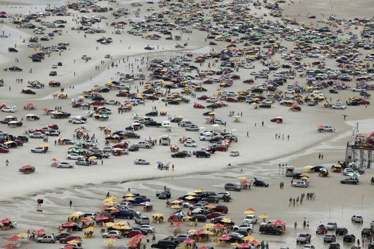 A view of thousands of beachgoers during the peak of the summer vacation season on Atalaia beach in Salinopolis, Para state, July 27, 2014. Salinopolis, with a population of 40,000, receives an estimated 280,000 visitors during the month of July, mostly to enjoy the beaches located just southeast of the Amazon river's mouth where the river's fresh water mixes with the Atlantic Ocean's salt water, tourism officials said. Officials estimate that close to 50,000 vehicles drive onto the city's two most popular beaches, Atalaia and Farol Velho, with tons of garbage left by visitors. Picture taken July 27, 2014. REUTERS/Paulo Santos