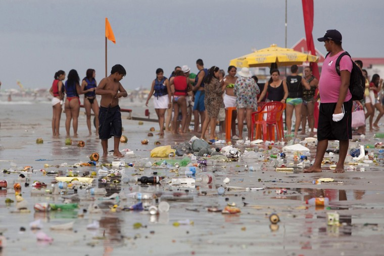 People stand next to trash during the peak of the summer vacation season on Atalaia beach in Salinopolis, Para state, July 27, 2014. Salinopolis, with a population of 40,000, receives an estimated 280,000 visitors during the month of July, mostly to enjoy the beaches located just southeast of the Amazon river's mouth where the river's fresh water mixes with the Atlantic Ocean's salt water, tourism officials said. Officials estimate that close to 50,000 vehicles drive onto the city's two most popular beaches, Atalaia and Farol Velho, with tons of garbage left by visitors. Picture taken July 27, 2014. REUTERS/Paulo Santos