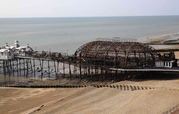 The burnt remains of a section of Eastbourne pier are seen in Eastbourne, southern England July 31, 2014. A Victorian-era seaside pier at Eastbourne on Britain's south coast was badly damaged when fire broke out in an amusement arcade on Wednesday. Flames could be seen leaping from the roof of the two-storey structure as a large plume of smoke rose above the town. No injuries were reported. REUTERS/Luke MacGregor